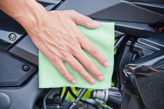 Hand with cleaning motorcycle. Hand with man cleaning motorcycle with green microfiber cloth Royalty Free Stock Photos