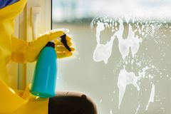 Hand cleaning window at home using detergent rag Stock Photography