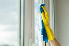 Hand cleaning window at home using detergent rag. Female hand in yellow gloves cleaning window with blue rag and spray detergent. Spring cleanup, housework stock image