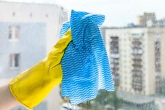 Hand cleans glass of home window in urban house. Hand cleans glass of home window in urban apartment house by blue rag stock image