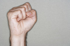Hand With Clenched Fist. Closeup of hand with clenched fist against gray background Royalty Free Stock Image