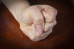 Hand clenched into a fist. Female hand clenched into a fist on a wooden table stock images