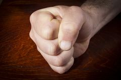 Hand clenched into a fist. Male hand clenched into a fist on a wooden table royalty free stock image