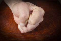 Hand clenched into a fist. Male hand clenched into a fist on a wooden table stock photos