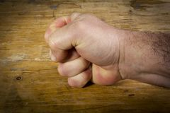 Hand clenched into a fist. Male hand clenched into a fist on a wooden table royalty free stock images