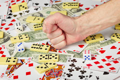 Hand clenched in a fist and playing cards Royalty Free Stock Photos