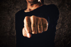Hand with clenched fist - tattooed hate. Hate. Hand with clenched fist on dark background. Power, determination, resistance concept Royalty Free Stock Photo