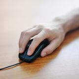 Hand clicking on a computer mouse Royalty Free Stock Photo