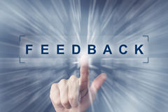Hand clicking on feedback button. With zoom effect background Stock Image