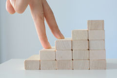 Hand climbing stairs made by wooden blocks. Hand ascending on a staircase made by wooden blocks, suggesting personal and professional growth Stock Photography