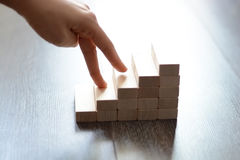 Hand climbing stairs made by wooden blocks. Suggesting professional or personal growth Stock Images