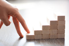 Hand climbing stairs made by wooden blocks. Symbolizing the ascendance of one's career Royalty Free Stock Photography