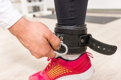 Hand Clipping Fastener to Ankle Strap in Gym. Close Up of Hand Clipping Fastener to Ankle Strap of Young Woman Wearing Bright Colored Running Shoe in Gym royalty free stock photography