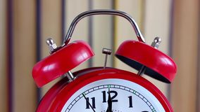 The hand on the clock is approaching twelve. Midnight, noon. Red classic alarm clock. New year stock footage