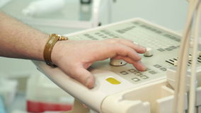 The hand with the clock on the wrist controls the ultrasound panel. stock footage