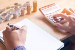 Hand close up, Calculating finances and calculate on table at home office. Hand close up, writing paper,Calculating finances and calculate  on table at home stock image