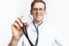 Hand close-up holding stethoscope, Portrait of young doctor on white background royalty free stock photo