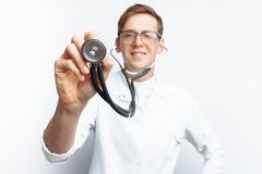 Hand close-up holding stethoscope, Portrait of young doctor on white background stock photos