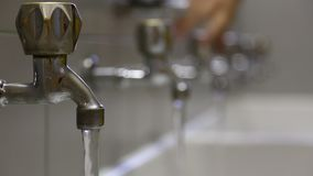 Handclosesmanyfaucetsto preventwaterwastage stock footage