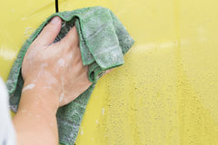 Hand with cloth cleaning dirty car. Car wash Royalty Free Stock Photo