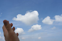 Hand and cloudy sky. A hand reaching out to the cloudy sky royalty free stock photos