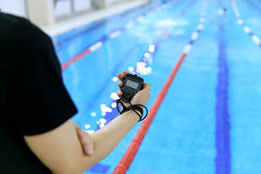 Hand of coach with a stopwatch during competitions in the swimming pool. Royalty Free Stock Image