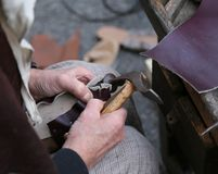 Cobbler repairs the shoe with an ancient hammer and the piece of. Hand of the cobbler repairs the shoe with an ancient hammer and the piece of leather royalty free stock photography