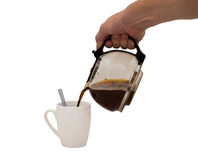 Hand & Coffee. An isolated over white image of a caucasian man's hand holding and pouring coffee into a white mug complete with spoon royalty free stock image