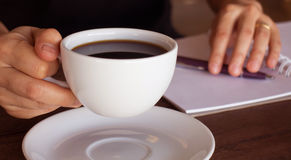Hand on coffee cup and smartphone Royalty Free Stock Photo