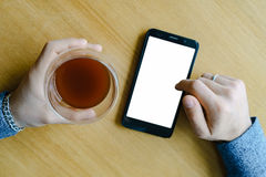 Hand coffee in glass smartphone male in cafe. Male hand with coffee in glass and smartphone in cafe Royalty Free Stock Photo