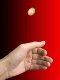 Hand and coin (choice). On blur (black-red) background stock photography