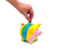 Hand with coin over a piggy bank Stock Photo