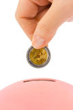 Hand with coin and piggy bank Stock Images