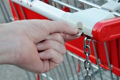 Hand with coin. Is taking a shopping cart Royalty Free Stock Photography