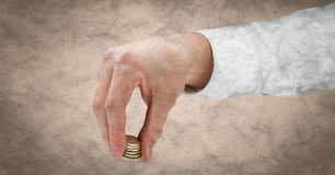 Hand with coins against cream grunge background Stock Image