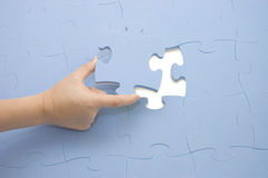 Hand collecting a part of a puzzle Stock Photos