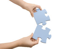 Hand collecting a part of a puzzle Royalty Free Stock Image