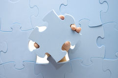 Hand collecting a puzzle Royalty Free Stock Image