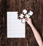 Hand collecting white puzzle on brown background Royalty Free Stock Photos