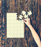 Hand collecting white puzzle on brown background Stock Photos