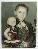 Hand-colored girl's photo with doll. Circa 1950 stock images
