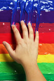 Hand in colorful paints Stock Image