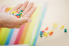 Hand with colorful pushpins Stock Photography
