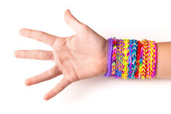 Hand with colorful rubber rainbow loom bracelets on white Royalty Free Stock Photography