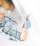 Hand coloring wall with paintbrush Royalty Free Stock Image