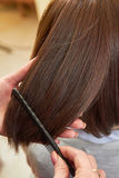 Hand with comb brushing hair. Stock Image