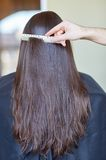 Hand with comb combing woman hair at salon Stock Images