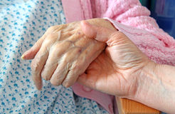 Hand Of Comfort. Photo of a carer giving a helping hand to an elderly person Stock Photos
