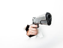 Hand coming through hole with big gun Royalty Free Stock Photography