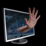 Hand coming out of a computer monitor. Royalty Free Stock Photography